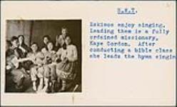 MIKAN 5196077 [Kaye Gordon leading six Inuit women in singing hymns]. [between 1955-1963] [[Kaye Gordon leading six Inuit women in singing hymns]., [between 1955-1963]]