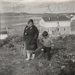 MIKAN 5196082 [Inuk woman and one of the Houston boys walking up a hill]. 1960 [[Inuk woman and one of the Houston boys walking up a hill]., 1960]