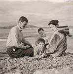 MIKAN 5196085 [The Houston family sitting on a rocky beach]. 1960 [[The Houston family sitting on a rocky beach]., 1960]