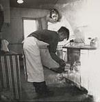 MIKAN 5196089 [Alma Houston watching an Inuk baker remove bread from an oven]. 1960 [[Alma Houston watching an Inuk baker remove bread from an oven]., 1960]