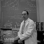 MIKAN 5196107 [Dr. Bert Migicovsky perched on the edge of a desk in a lab]. [ca. 1962] [[Dr. Bert Migicovsky perched on the edge of a desk in a lab]., [ca. 1962]]