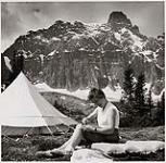 MIKAN 5196108 [Female member of the Alpine Club of Canada sitting on an air mattress next to a tent cutting her pants with scissors]. [between 1953-1964] [[Female member of the Alpine Club of Canada sitting on an air mattress next to a tent cutting her pants with scissors]., [between 1953-1964]]
