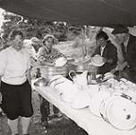 MIKAN 5196118 [Four members of the Alpine Club of Canada, one male and three female, wash dishes under a tent]. [between 1953-1964] [[Four members of the Alpine Club of Canada, one male and three female, wash dishes under a tent]., [between 1953-1964]]