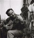 MIKAN 5196124 [Man playing guitar in a tent]. [between 1953-1964] [[Man playing guitar in a tent]., [between 1953-1964]]