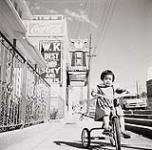 MIKAN 5196133 [Young Asian girl riding a tricycle with W.K. Best Chop Suey and Noodles Restaurant in the background]. 1957 [[Young Asian girl riding a tricycle with W.K. Best Chop Suey and Noodles Restaurant in the background]., 1957]