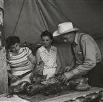 MIKAN 5196138 [Two women, and a man wearing a cowboy hat, carving meat]. [between 1953-1964] [[Two women, and a man wearing a cowboy hat, carving meat]., [between 1953-1964]]