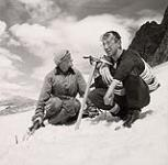 MIKAN 5196140 [Portrait of two male mountaineers, one with rope over his shoulder, sitting on snow]. [between 1953-1964] [[Portrait of two male mountaineers, one with rope over his shoulder, sitting on snow]., [between 1953-1964]]