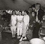 MIKAN 5196174 [Group assembled in a tent with a man playing a guitar]. [between 1953-1964] [[Group assembled in a tent with a man playing a guitar]., [between 1953-1964]]