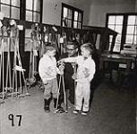 MIKAN 5196176 [Paul Lajoie helps two little boys choose the right size ski poles]. [between 1953-1964] [[Paul Lajoie helps two little boys choose the right size ski poles]., [between 1953-1964]]