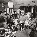 MIKAN 5196178 [A man, woman, and young boy, stand at the check-out counter at a ski equipment gear-swap]. [between 1953-1964] [[A man, woman, and young boy, stand at the check-out counter at a ski equipment gear-swap]., [between 1953-1964]]