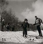MIKAN 5196180 [Young boy with his hood up and smiling, sets off down a hill skiing as a male instructor watches]. [between 1953-1964] [[Young boy with his hood up and smiling, sets off down a hill skiing as a male instructor watches]., [between 1953-1964]]