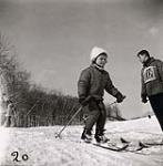 MIKAN 5196182 [Young girl wearing light coloured, fluffy winter hat, sets off down a hill skiing as a male instructor watches]. [between 1953-1964] [[Young girl wearing light coloured, fluffy winter hat, sets off down a hill skiing as a male instructor watches]., [between 1953-1964]]