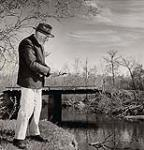 MIKAN 5196199 [An elderly Mennonite settler fishes in a river near Steinbach]. 1955 [[An elderly Mennonite settler fishes in a river near Steinbach]., 1955]