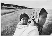MIKAN 4322676 [Femme inuk Angugasak Kadloo portant Lamechie Kadloo (Kalluk) dans son amauti (parka) à Mittimatalik] Titre original: Femme autochtone portant un jeune garçon sur le dos à côté d'un plan d'eau  s.d. [104 KB, 1000 X 686]
