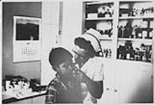 MIKAN 4322262 Nurse examining the ear of young Aboriginal boy. n.d. [Nurse examining the ear of young Aboriginal boy., n.d.]