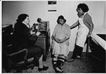 MIKAN 4322265 Pregnant Aboriginal woman [Jayko Pitsiulak] seated beside nurse and Aboriginal woman [Leah Idlout] wearing white apron  n.d. [109 KB, 1000 X 694]
