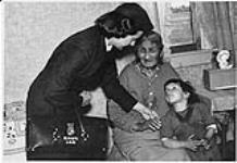 MIKAN 4322318 Small child looking up at Public Health Nurse Miss Stantin (?) taking the hand of elderly Aboriginal woman, Fisher River, Manitoba . n.d. [122 KB]