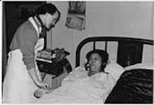MIKAN 4322320 Nurse administering medication to Aboriginal woman lying in bed. n.d. [Nurse administering medication to Aboriginal woman lying in bed., n.d.]