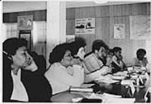 MIKAN 4322335 Group of Aboriginal men and women seated at desks during home nursing program. n.d. [111 KB]