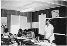 MIKAN 4322336 Nurse teaching a group of Aboriginal men and women seated at tables during home nursing program. n.d. [108 KB]