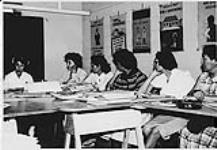 MIKAN 4322337 Nurse teaching a group of Aboriginal  women seated at tables during home nursing program. n.d. [Nurse teaching a group of Aboriginal women seated at tables during home nursing program., n.d.]