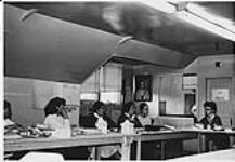 MIKAN 4322338 Nurse teaching a group of Aboriginal  women seated at tables during home nursing program. n.d. [Nurse teaching a group of Aboriginal women seated at tables during home nursing program., n.d.]