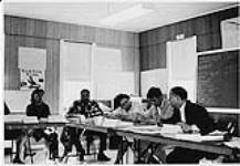 MIKAN 4322339 Group of Aboriginal men and women seated at desks during home nursing program. n.d. [119 KB]