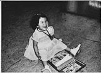 MIKAN 4322418 Young Aboriginal girl seated on the floor playing with a toy nurse kit (?) n.d. [Young Aboriginal girl seated on the floor playing with a toy nurse kit (?), n.d.]