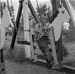 MIKAN 4308113 Garçon sur une balançoire en forme de cheval, Flin Flon, Manitoba  juin 1956. [Garçon sur une balançoire en forme de cheval, Flin Flon, Manitoba, juin 1956.]