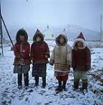 MIKAN 4324138 Four young Inuit girls wearing parkas outdoors, Salluit, Quebec. [Left to right: Eva (Alaku) Kuananck, Annie Qupirqualuk, Laly (Saviadjuk) Kumakuluk and Siasie (Qalingo) Manguik.]  [ca. 1955-1963] [188 KB, 1000 X 1007]