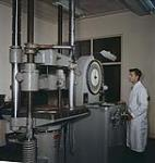MIKAN 4313913 A test being made on some alumimun in the testing laboratory. Kingston, Ontario.  [Test effectué sur de l'aluminium dans un laboratoire. Kingston, Ontario.] 1957 [A test being made on some alumimun in the testing laboratory. Kingston, Ontario., 1957]