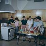 MIKAN 4301844 A Home Economics class receiving instructions on cooking. Ottawa, Ont.  1959 [164 KB, 1000 X 1009]