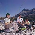 MIKAN 4302085 Art Gault assisting Jimmy with fishing gear at Waterton Lakes National Park, Alberta.  August 1961 [217 KB, 1000 X 1012]