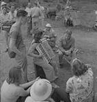 MIKAN 4325099 Captain of the clouds, group around a woman playing an accordion. North Bay, Ontario. August, 1941 [152 KB, 1000 X 1055]