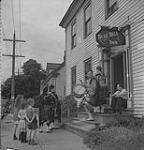 MIKAN 4325931 Les Highland Games, Antigonish, 1940, enfants et joueurs de cornemuse à l'extérieur du Blue Bell Inn. 1940 [200 KB, 1000 X 1041]