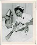 MIKAN 4366006 Infirmière Betty Hutchinson aidant Harold Hawkins à exercer les muscles de ses mains en attachant des boutons. Western Hospital de Toronto. Infirmières et soins. Ministère de la Citoyenneté et de l'Immigration, division de l'information. [entre 1930-1960] [173 KB, 1000 X 1221]