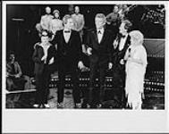 MIKAN 4384018 TommyHunter (au centre), PatBoone (?), Little Jimmy Dickens et CarrollBaker (?), debout sur scène avec deuxhommes, à l¿arrière de la scène, un groupe de musique  [ca 1982]. [118 KB, 1000 X 793]