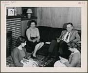 MIKAN 4365420 Herbert Jones reading a magazine in his home while his wife and daughters Angela Mary and Lindsay play cards nearby. [between 1957-1960] [Herbert Jones reading a magazine in his home while his wife and daughters Angela Mary and Lindsay play cards nearby., [between 1957-1960]]