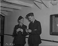 MIKAN 4327487 Two uniformed men talking and counting money during the arrival of the Australians in Vancouver, British Columbia  September 26, 1940 [Two uniformed men talking and counting money during the arrival of the Australians in Vancouver, British Columbia, September 26, 1940]