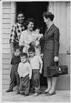 MIKAN 4322076 Aboriginal man and woman standing in doorway with four children and nurse, La Ronge, Saskatchewan. 1975 [157 KB]