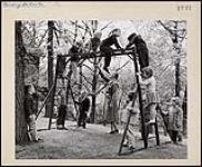 MIKAN 4365813 Enfants grimpant sur une structure de jeu à la prématernelle Miss Robinson, Winnipeg, Manitoba. 6 juin 1959 [Enfants grimpant sur une structure de jeu à la prématernelle Miss Robinson, Winnipeg, Manitoba., 6 juin 1959]