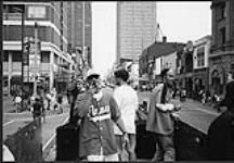 MIKAN 4382084 Earthtones, R & B group from Calgary, performing from a truck on a busy street  [between 1992-1997]. [Earthtones, R & B group from Calgary, performing from a truck on a busy street, [between 1992-1997].]