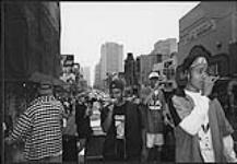 MIKAN 4382087 Earthtones, R & B group from Calgary, performing from a truck on a busy street  [between 1992-1997]. [118 KB, 1000 X 691]