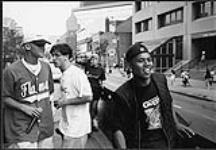 MIKAN 4382088 Earthtones, R & B group from Calgary, performing from a truck on a busy street  [between 1992-1997]. [112 KB, 1000 X 692]