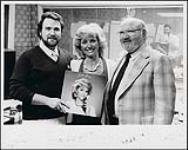 MIKAN 4381484 Wayne Cavanagh of K-96 FM with Audie Henry and producer Bart Burton, holding Audie Henry's album. [between 1985-1986]. [Wayne Cavanagh of K-96 FM with Audie Henry and producer Bart Burton, holding Audie Henry's album., [between 1985-1986].]