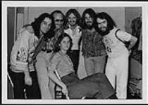 MIKAN 4381631 Members of the Hometown Band posing in a group - five men with arms on each others' shoulders, Shari Ulrich sitting in a chair  [between 1976-1977]. [Members of the Hometown Band posing in a group - five men with arms on each others' shoulders, Shari Ulrich sitting in a chair, [between 1976-1977].]