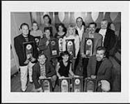 MIKAN 4430497 LeAnn Rimes recevant plusieurs prix qu'elle montre accompagnée de Deane Cameron et d'autres personnes  [entre 1995-2000]. [137 KB, 1000 X 798]