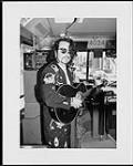 MIKAN 4430057 Unidentified man playing guitar on a bus. (publicity photo)  [between 1980-2000]. [144 KB, 1000 X 1242]