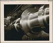 MIKAN 4369885 Un homme qui tourne l'arbre d'une centrale hydro-électrique de trente tonnes sur un tour à l'usine de la Générale électrique du Canada, à Peterborough  [entre 1930-1960] [Un homme qui tourne l'arbre d'une centrale hydro-électrique de trente tonnes sur un tour à l'usine de la Générale électrique du Canada, à Peterborough, [entre 1930-1960]]