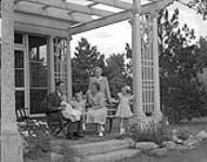 MIKAN 4759526 H.R.H. Princess Juliana with Queen Wilhelmina, Prince Bernhard, and 3 Princesses at house, July 1, 1943  1943. [H.R.H. Princess Juliana with Queen Wilhelmina, Prince Bernhard, and 3 Princesses at house, July 1, 1943, 1943.]